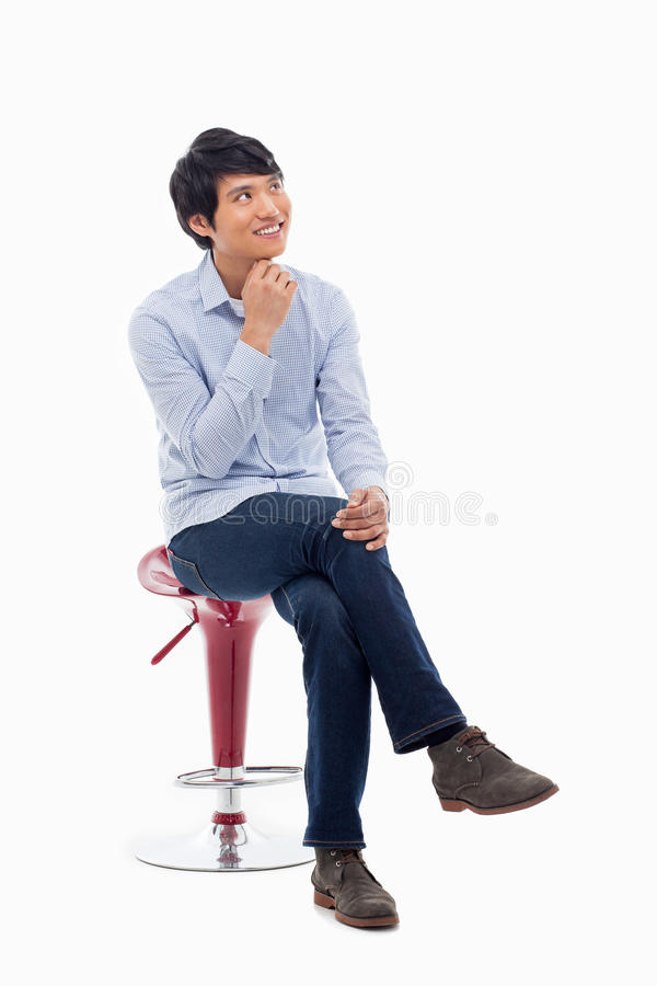 Junger asiatischer Mann, der auf dem Stuhl denkt. stockbild