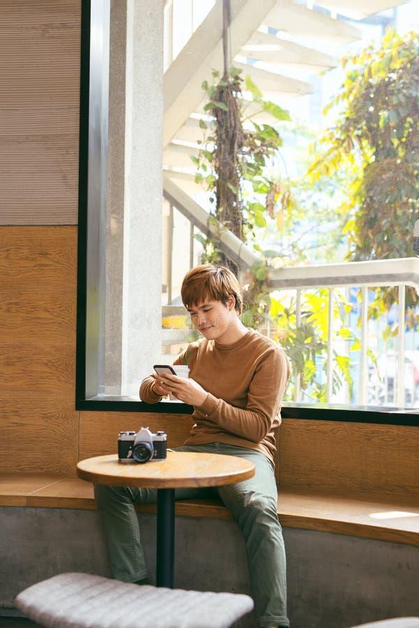 Junger asiatischer Mann, der intelligentes Telefon während des Frühstückens, coffe verwendet stockfotos