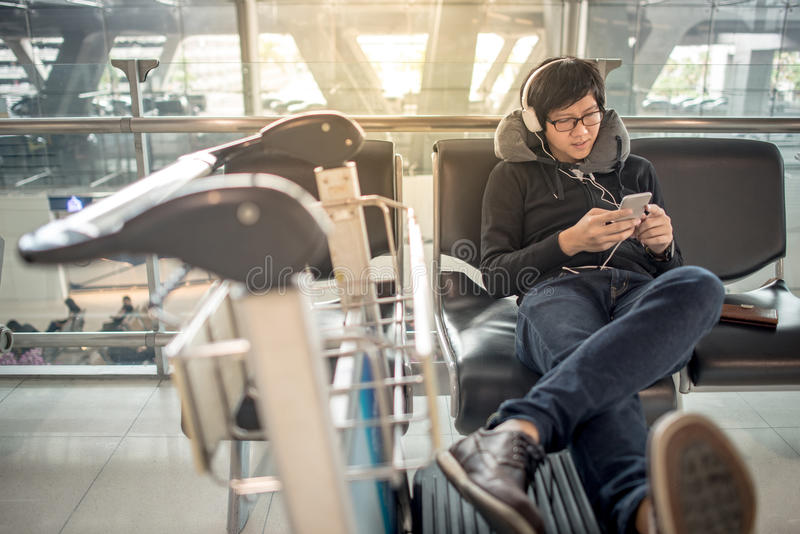 Junger asiatischer Mann, der Musik bei der Aufwartung in Flughafen hört stockbilder
