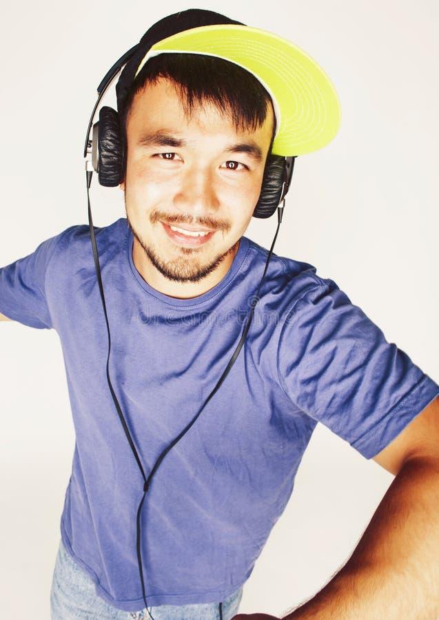 Junger asiatischer Mann in h?render Musik des Hutes und der Kopfh?rer auf wei?em Hintergrund lizenzfreies stockbild