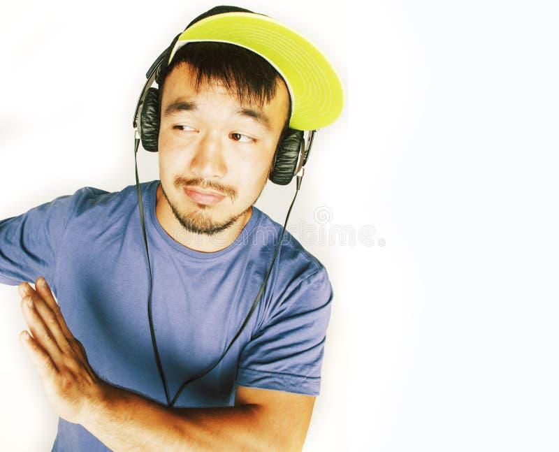 Junger asiatischer Mann in h?render Musik des Hutes und der Kopfh?rer auf wei?em Hintergrund stockbild