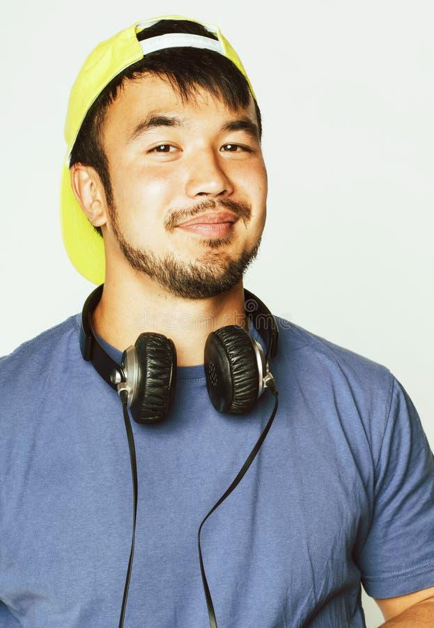 Junger asiatischer Mann in h?render Musik des Hutes und der Kopfh?rer auf wei?em Hintergrund lizenzfreie stockbilder