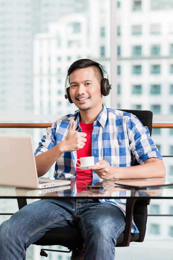 Junger asiatischer Mann im Büro, das den Kaffee gibt Daumen trinkt, up Zeichen lizenzfreies stockbild