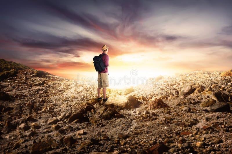 Junger asiatischer Mann mit dem Rucksack, der in den felsigen Bergen wandert lizenzfreie stockfotografie