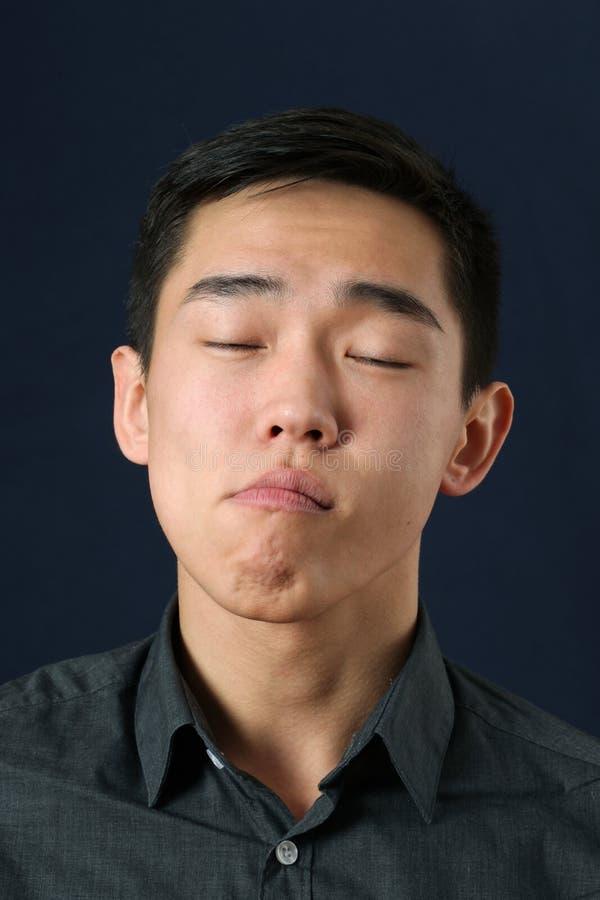 Junger asiatischer Mann mit geschlossenen Augen lizenzfreie stockfotos