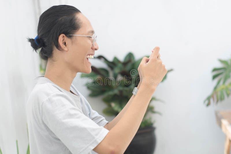 Junger asiatischer Mann unter Verwendung des Smartphone und aufgeregter, junger asiatischer Mann erhalten, der Spiel am Smartphon stockfotografie