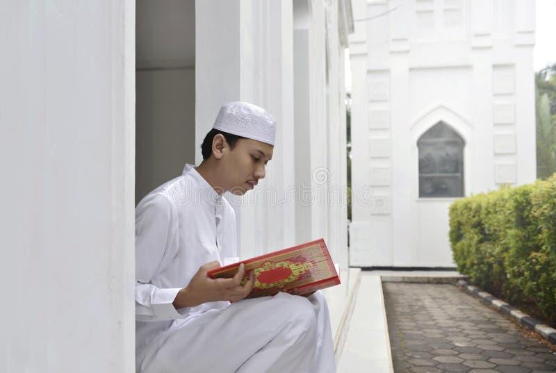Junger asiatischer moslemischer Mann, der den Quran der Heiligen Schrift liest stockfotos