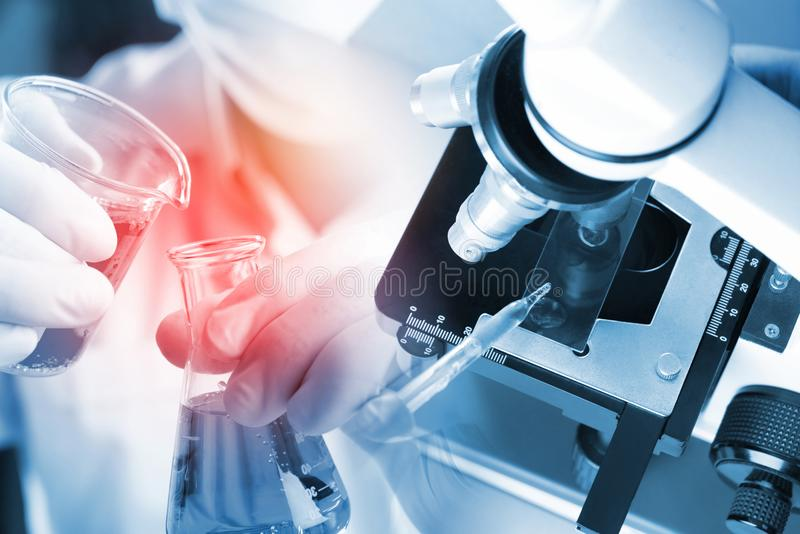 Junger asiatischer Studentenjunge und weißes Mikroskop im Wissenschaftslabor mit roter Flüssigkeit und Tropfenzähler für die Prüf lizenzfreie stockfotos