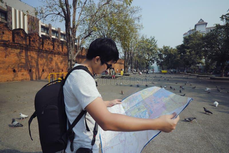 Junger asiatischer Tourist mit Rucksacktasche eine Karte in Tor Tha Phae, Chiang Mai, Thailand erforschend stockbilder