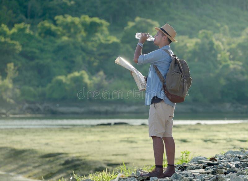 Junger asiatischer touristischer Mann mit Trinkwasser des Rucksacks lizenzfreie stockbilder