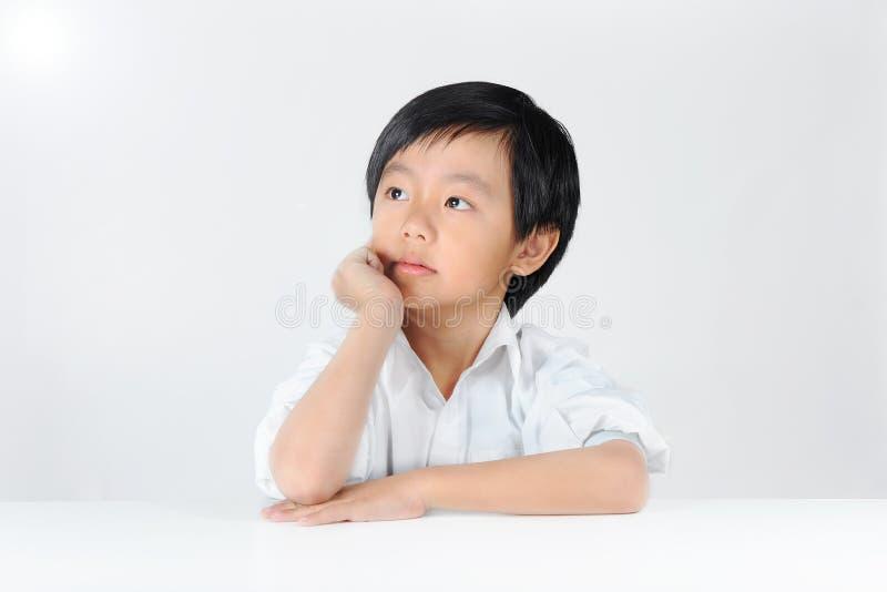 Junger asiatischer träumender Schüler stockbild