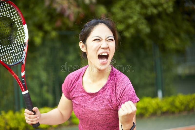 Junger asiatischer weiblicher Tennisspieler, der nachdem dem Zählen feiert stockbild