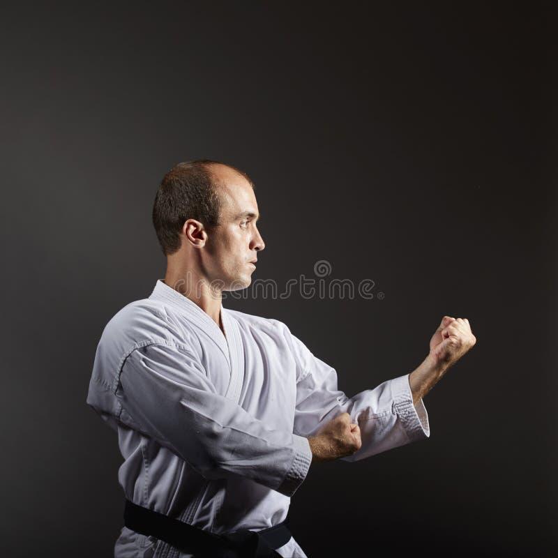 Junger Athlet bildet formale Karateübungen auf einem schwarzen Hintergrund aus lizenzfreie stockfotografie