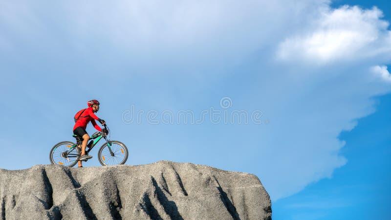 Junger Athlet, der auf einem Felsen mit Fahrrad steht Radfahrerreitmountainbike auf der felsigen Spur bei Sonnenuntergang Extreme stockfotografie