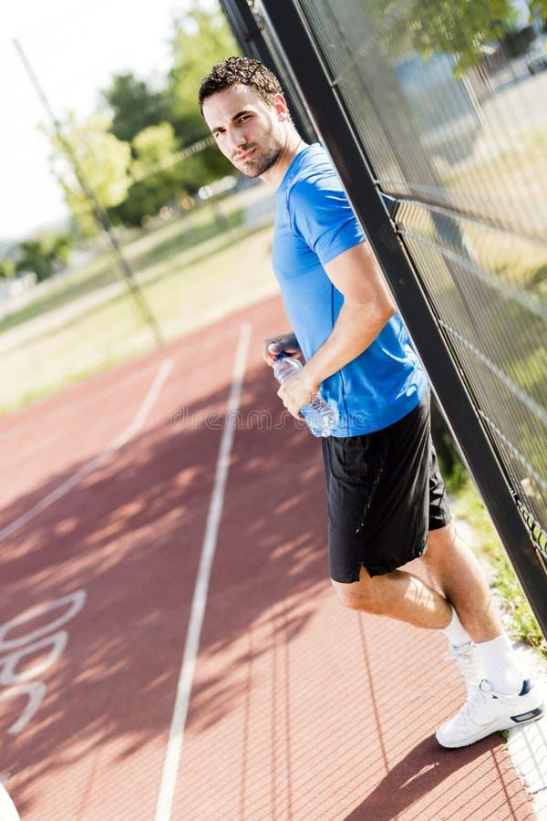 Junger Athlet, der eine Pause an einem heißen Sommertag macht lizenzfreie stockfotos
