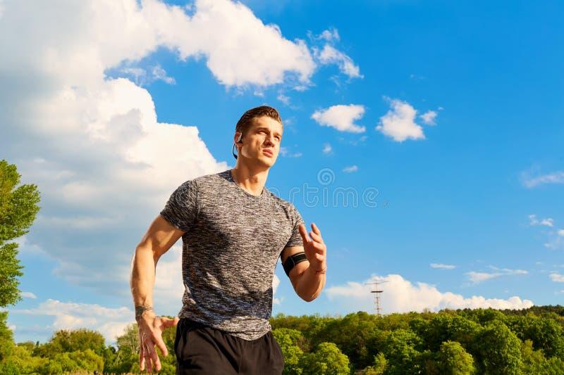 Junger Athlet, der am Hintergrund des blauen Himmels läuft lizenzfreie stockbilder