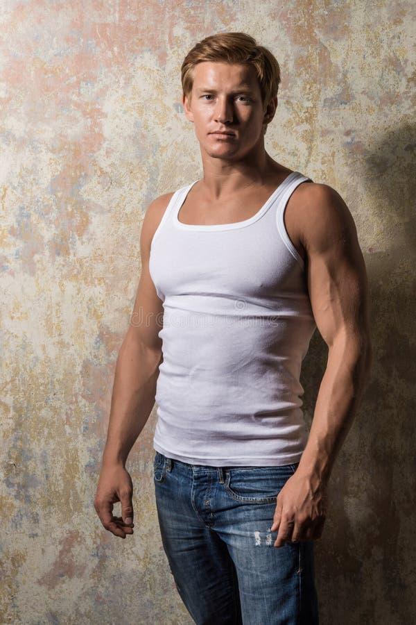 Junger Athlet, der leere weiße Weste, ärmelloses T-Shirt trägt stockfotos