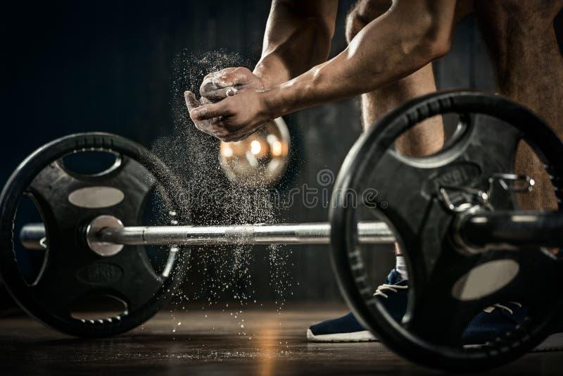 Junger Athlet, der zum Gewichthebentraining fertig wird Powerlifter-Hand im Talkum, das zum Bankdrücken sich vorbereitet stockbild