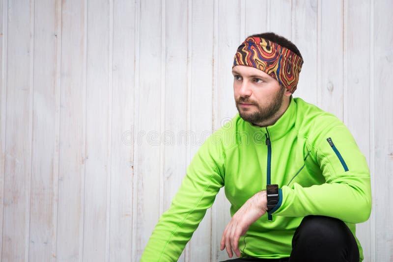 Junger Athlet des europäischen Auftrittes in einer grünen Jacke, Uhr, schwarze Hosen, sitzt stockfotografie