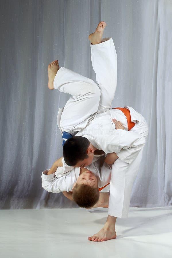 Junger Athlet mit einem orange Gurt führt Technik nage-waza durch stockbild