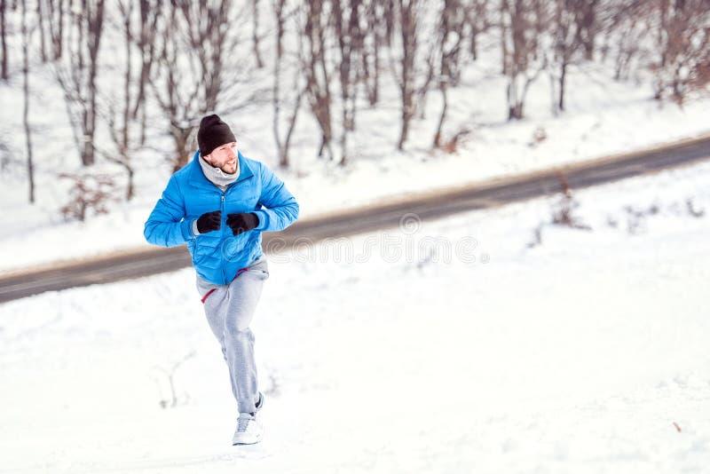 Junger Athletenmann, der auf Schnee für ein gesundes Training läuft stockbilder