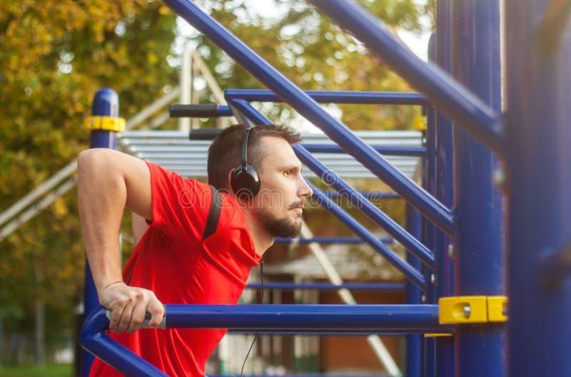 Junger athletischer Mann, der draußen Sportübungen im Park tut lizenzfreie stockfotos