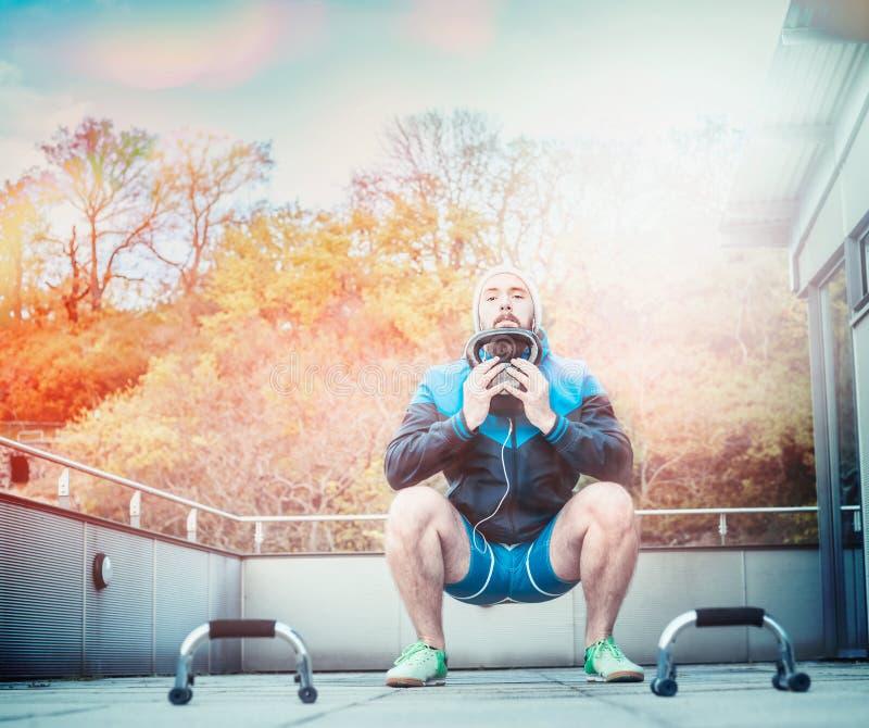 Junger athletischer Mann, der Hockegewichte in seinen Händen, auf der Terrasse ihres Hauses, auf einem Hintergrund Sonnenuntergan lizenzfreies stockbild