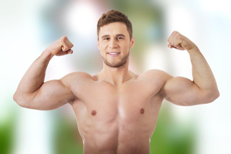 Junger athletischer Mann, der seine Muskeln zeigt stockfotografie
