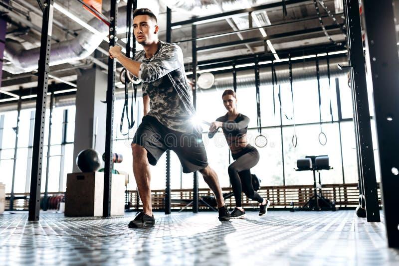 Junger athletischer Mann und dünnes Mädchen tun Sportübungen mit spezieller Ausrüstung wie Machtband in der Turnhalle stockbild