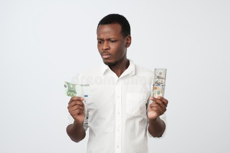 Junger attraktiver afrikanischer Mann, der USA-Währung und Eurowährung welches entscheiden, um zu wählen hält lizenzfreies stockbild