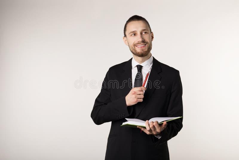 Junger attraktiver bärtiger Lehrer im schwarzem Anzug und Bindungsholdingnotizbuch und Stift in den Händen lizenzfreie stockbilder