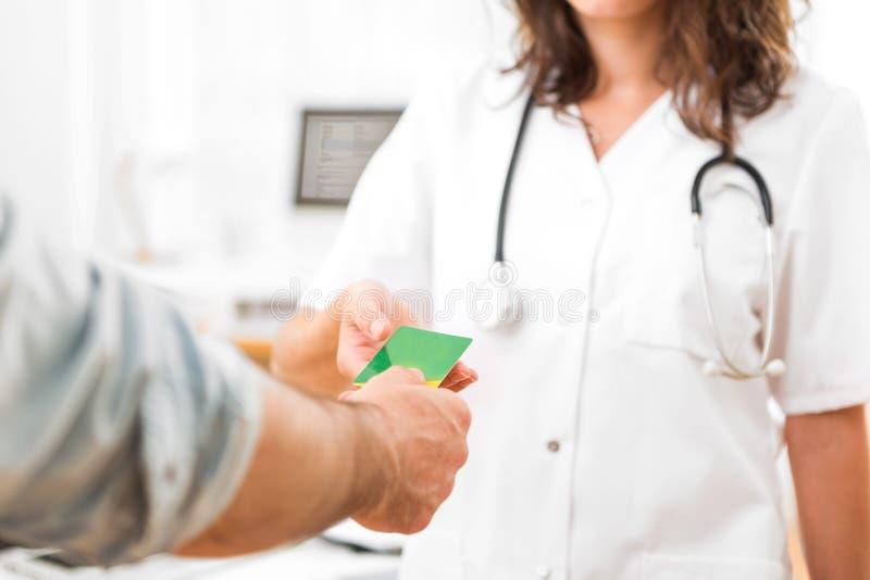 Junger attraktiver Doktor, der Krankenversicherungskarte nimmt stockfoto