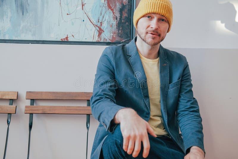 Junger attraktiver erwachsener bärtiger Mannhippie im gelben Hut, der auf Stuhl sitzt und Kamera, wirklichen Leutelebensstil betr stockfotos