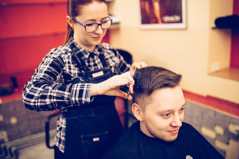 Junger attraktiver Frauenfriseur machen Frisur für Mann stockbild