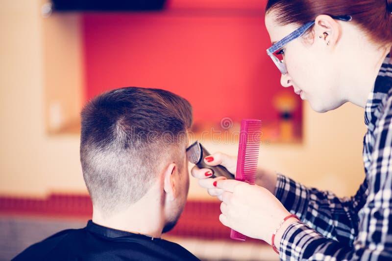 Junger attraktiver Frauenfriseur machen Frisur für Mann lizenzfreie stockbilder
