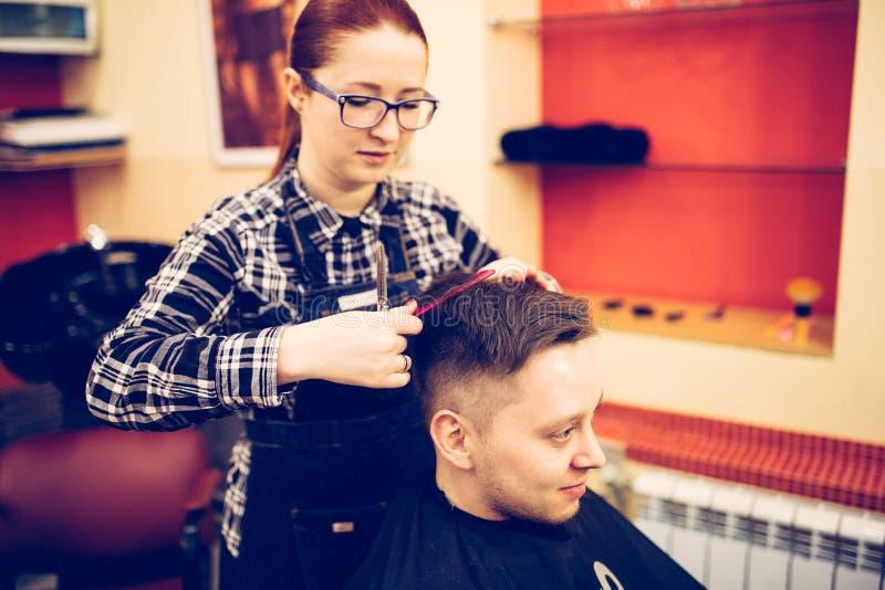 Junger attraktiver Frauenfriseur machen Frisur für Mann lizenzfreie stockfotos
