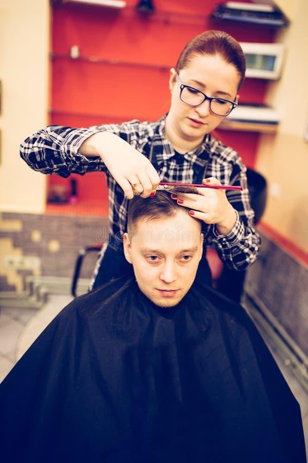 Junger attraktiver Frauenfriseur machen Frisur für Mann lizenzfreie stockfotografie