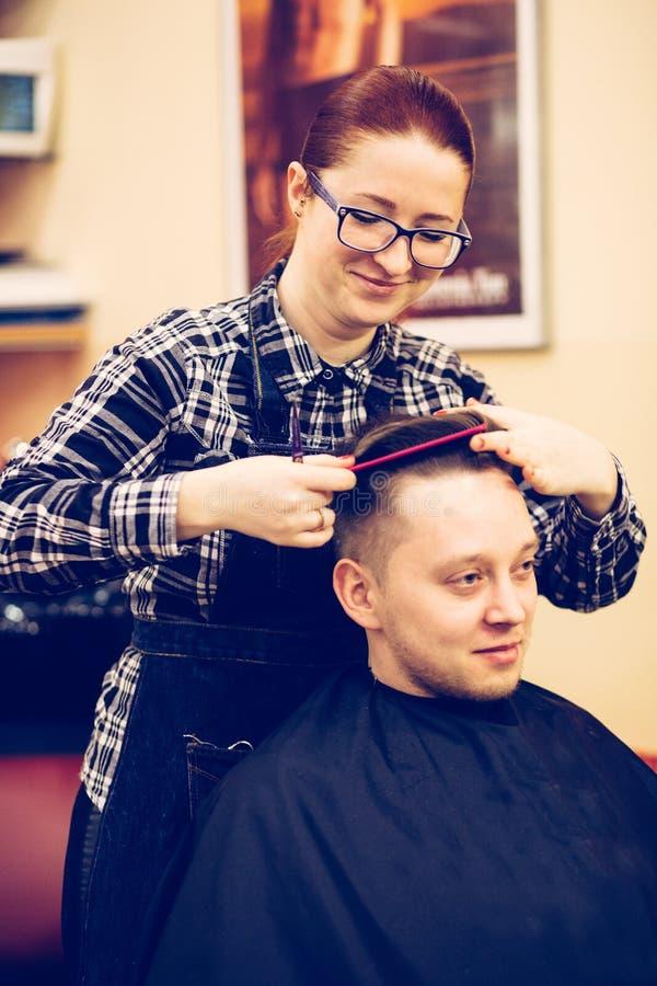 Junger attraktiver Frauenfriseur machen Frisur für Mann lizenzfreies stockfoto