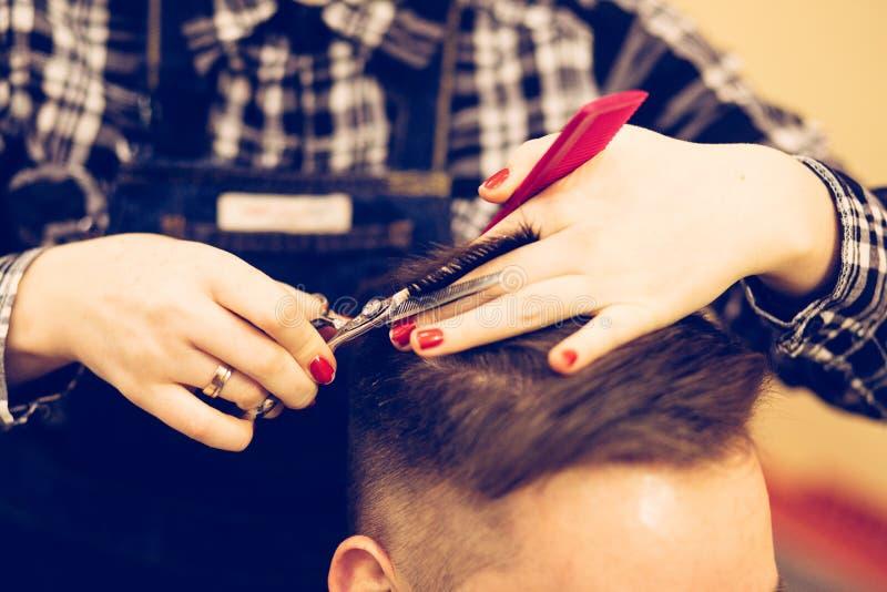 Junger attraktiver Frauenfriseur machen Frisur für Mann stockfotografie