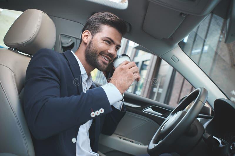 Junger attraktiver Geschäftsmann, im Autogetränkkaffee und an -sprechen stockfotografie