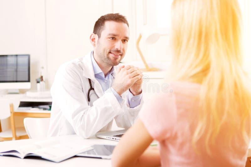 Junger attraktiver hörender Doktor sein Patient stockfoto