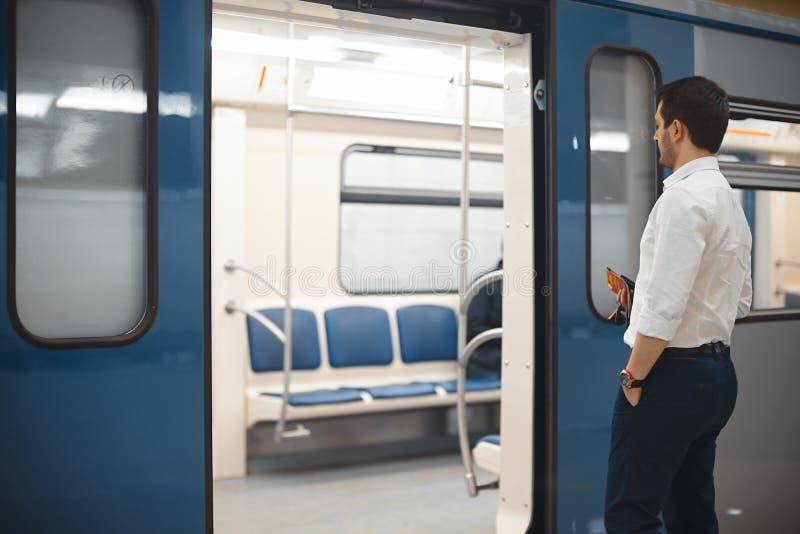 Junger attraktiver hereinkommender Zug des Geschäftsmannes oder des Managers in der Metro oder in der U-Bahn lizenzfreies stockbild