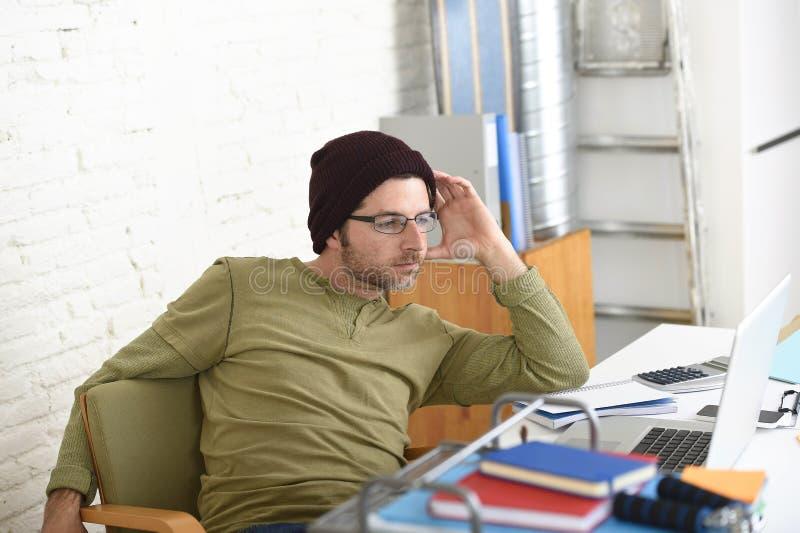 Junger attraktiver Hippie-Geschäftsmann, der von seinem Innenministerium als selbstständiges Geschäftsmodell des Freiberuflers ar lizenzfreies stockbild