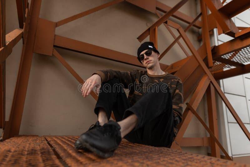 Junger attraktiver Hippie-Mann im stilvollen Hut in den Jeans in der dunklen Sonnenbrille im modischen Militärhemd in den lederne lizenzfreies stockbild