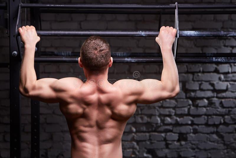 Junger attraktiver kaukasischer crossfit Sportler, der in der Turnhalle, hintere Ansicht ausarbeitet stockfoto