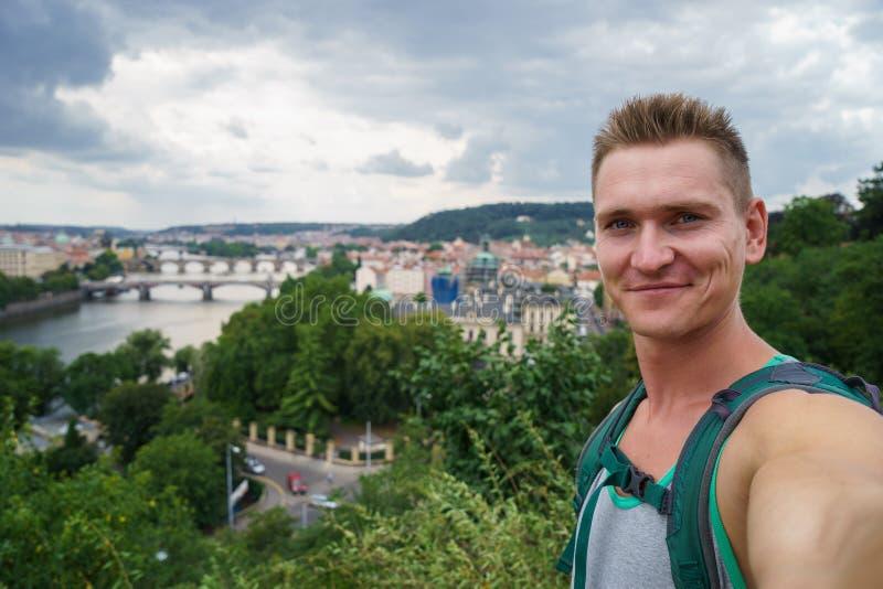 Junger attraktiver Kerl, der selfie mit Landschaftsansichtbrücken auf die Moldau-Fluss in Tschechischer Republik Prags nimmt lizenzfreie stockfotografie