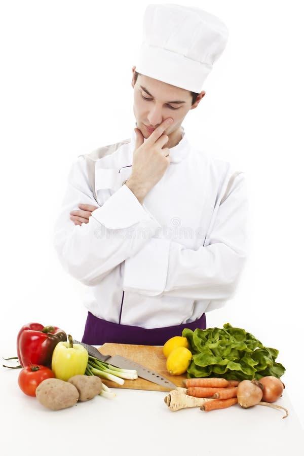 Junger attraktiver Mann, Chef, der was denkt zu kochen lizenzfreies stockfoto