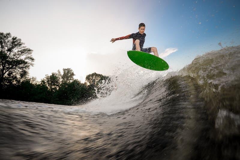 Junger attraktiver Mann, der auf das grüne wakeboard auf dem See springt stockfotografie