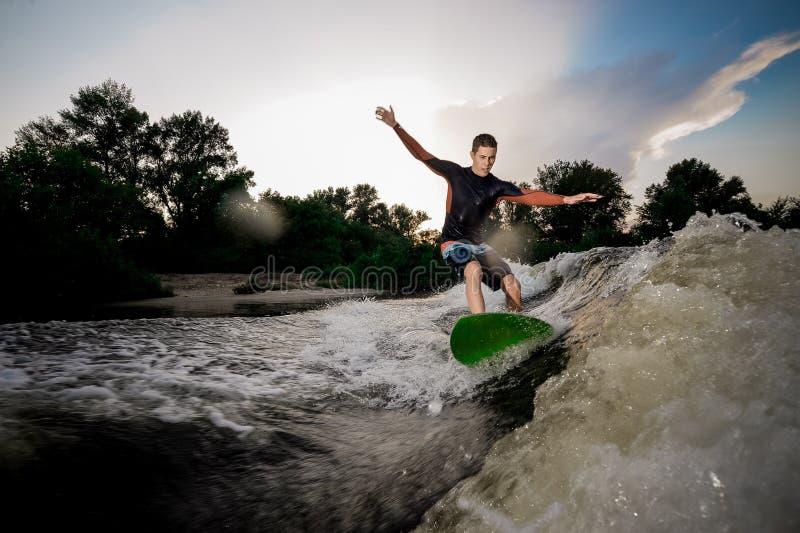 Junger attraktiver Mann, der auf das wakeboard auf dem See springt lizenzfreies stockbild