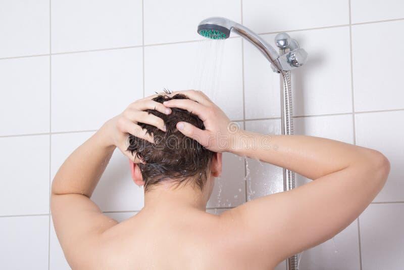 Junger attraktiver Mann, der eine Dusche nimmt stockfoto